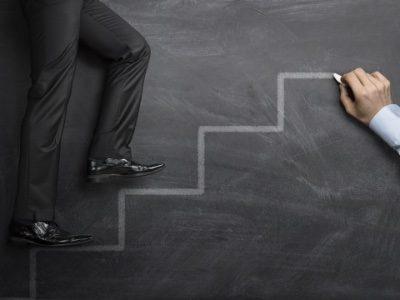 Businessman climbing the career steps drawn on a black chalkboard
